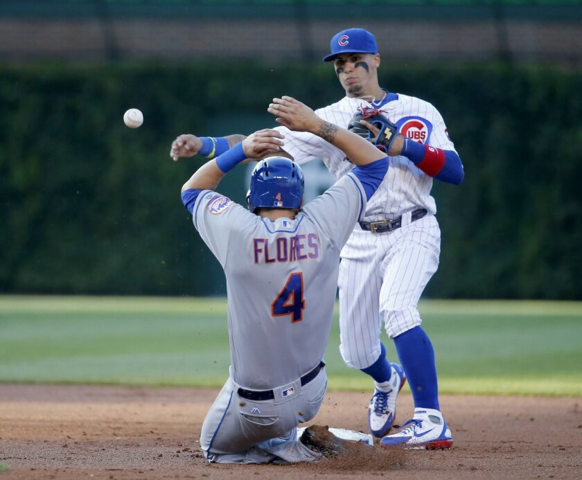 Chicago Cubs' Javier Baez, right, turns a double play, forcing New York Mets' Wilmer Flores (4) out at second and getting Asdrubal Cabrera at first, during the second inning of a baseball game Monday, July 18, 2016, in Chicago. (AP Photo/Charles Rex Arbogast)