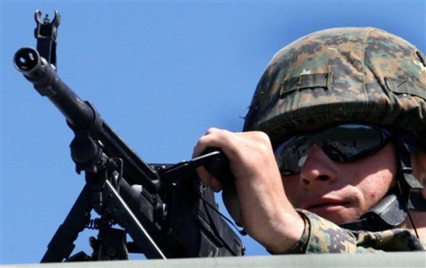 A Georgian machine gunner looks on during NATO training exercises at Vaziani military base outside Tbilisi, Georgia, Sunday May 31, 2009. Russia has sharply criticized the war games, saying they raise the threat of renewed conflict in the country 10 months after the Russia-Georgia war. (AP Photo/Sh