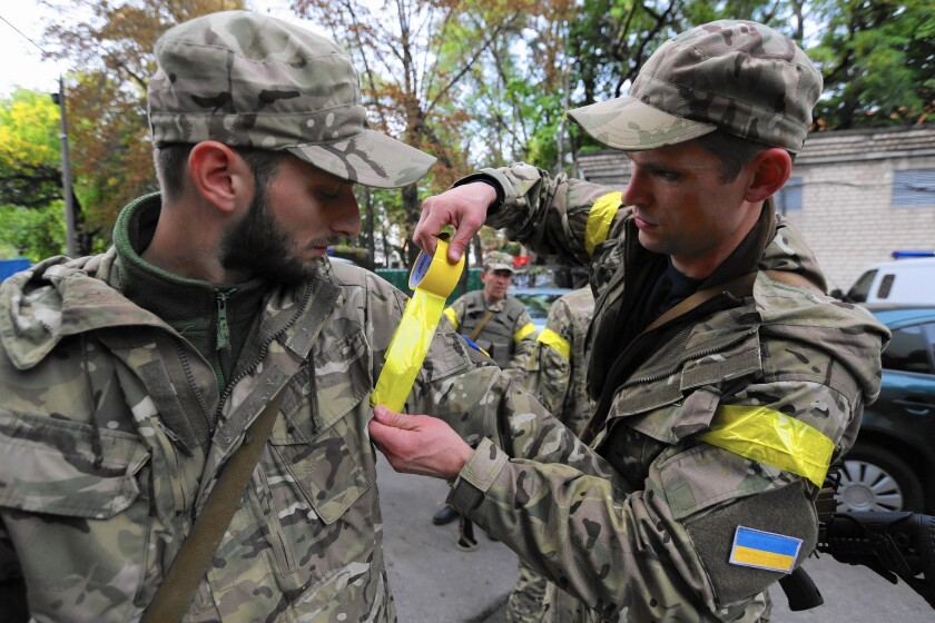 Ukraine soldiers put tape on their arms to identify themselves as comrades in the fight against pro-Russia separatists.