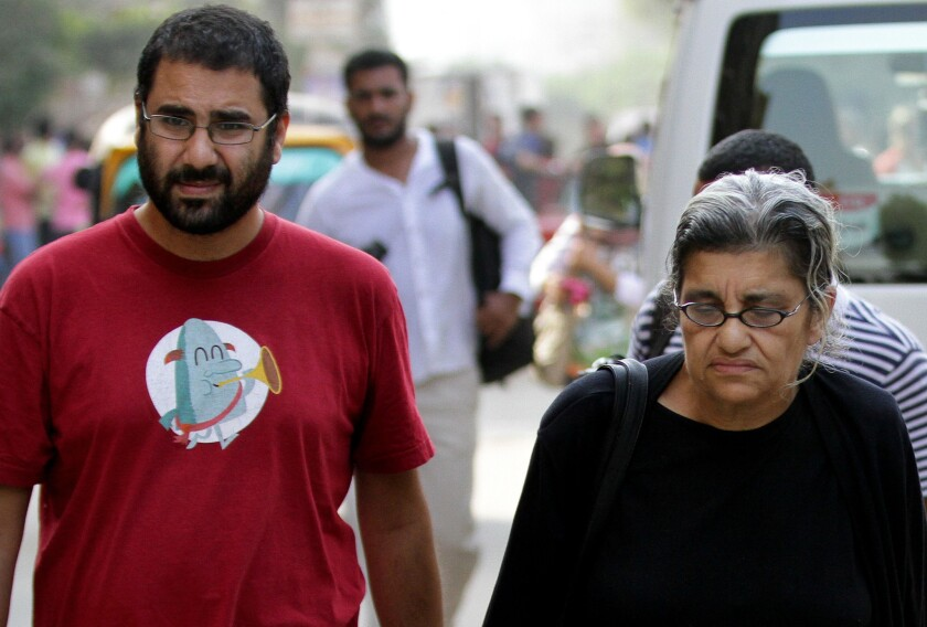 Egypt's most prominent activist, Alaa Abdel Fattah, left, walks with his mother, Laila Soueif, a university professor and activist, outside a court where 23 fellow activists were sentenced to prison for staging an illegal demonstration. Among the 23 was Abdel-Fattah's sister, Sanaa Seif.