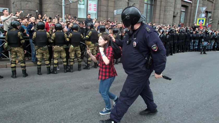 A Russian police officer detains a teenager during rally protesting retirement age hikes in St. Pete