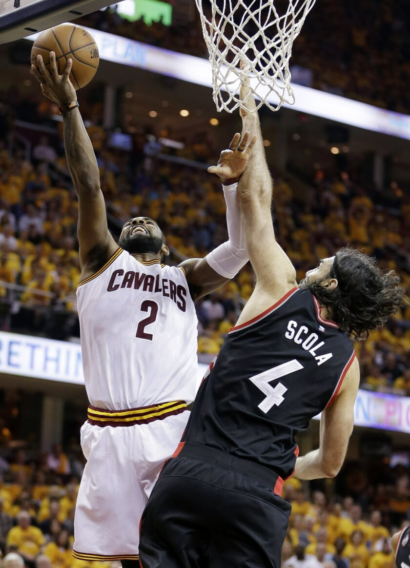 Cleveland Cavaliers' Kyrie Irving (2) shoots against Toronto Raptors' Luis Scola (4), from Argentina, during the second half of Game 5 of the NBA basketball Eastern Conference finals Wednesday, May 25, 2016, in Cleveland. (AP Photo/Tony Dejak)