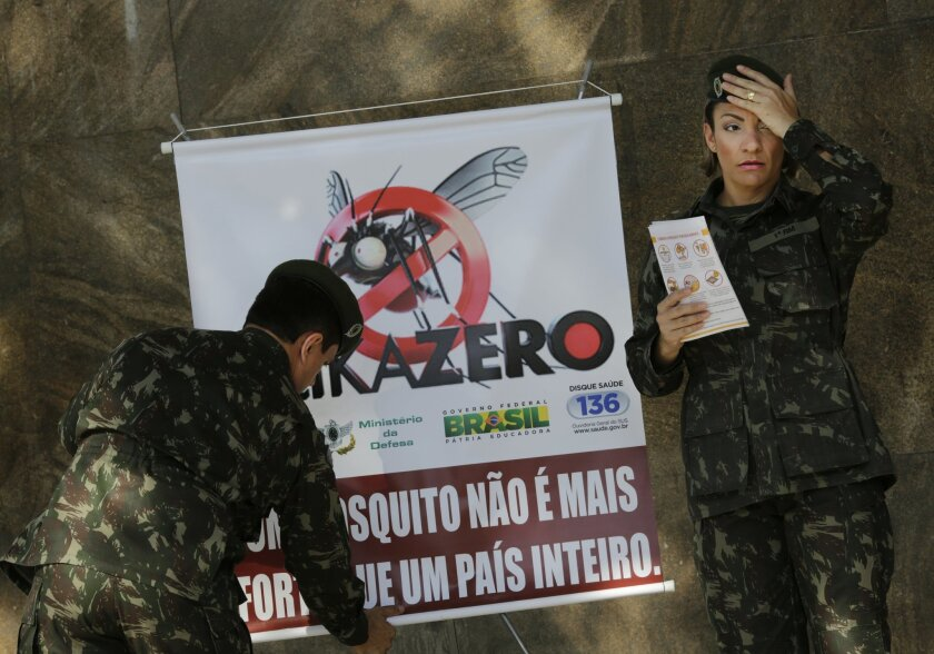 "Army soldiers set a banner that reads in Portuguese ""A mosquito is not stronger than a whole country"" at the Central station, in Rio de Janeiro, Brazil, Saturday, Feb. 13, 2016. More than 200,000 army, navy and air force troops are fanning out across Brazil to show people how to eliminate the Aedes"