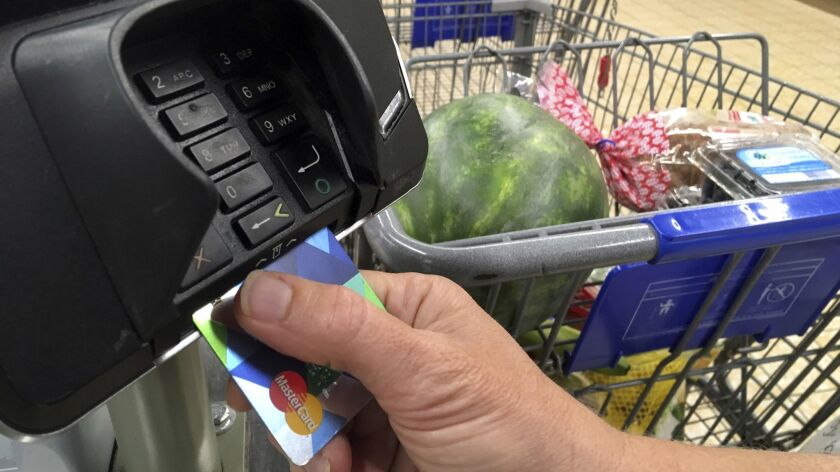 In this July 17, 2018 photo, a customer buys groceries with a credit card in Salem, N.H. (AP Photo/E