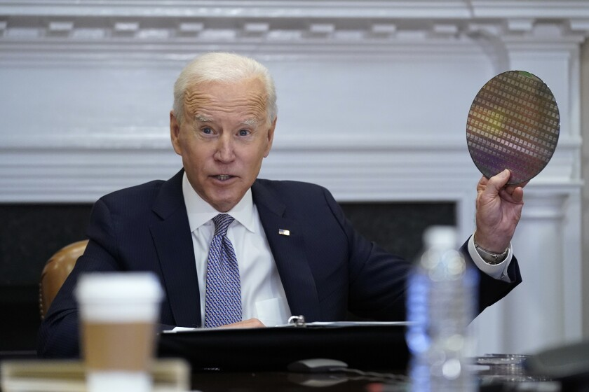 President Biden holds up a silicon wafer as he participates virtually in a meeting at the White House.