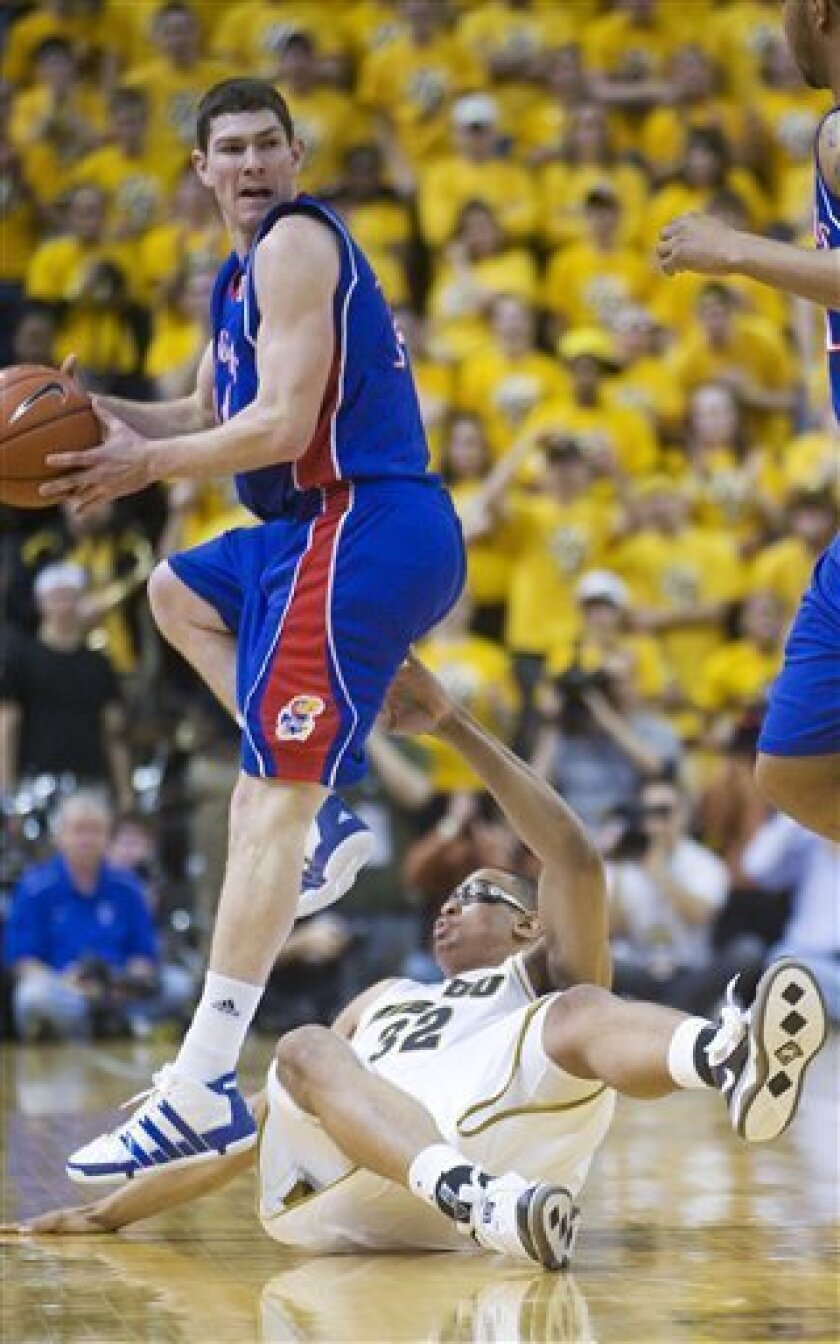 Kansas's Brady Morningstar, left, looks to pass as Missouri's Steve Moore, bottom, falls to the court during the first half of an NCAA college basketball game Saturday, March 6, 2010, in Columbia, Mo. (AP Photo/L.G. Patterson)