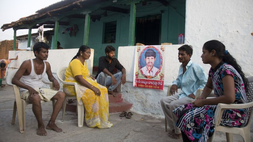 Family member grieve by a portrait of Bala Krishna, a 33-year-old motorized rickshaw driver who was