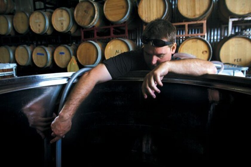 Adam Carruth transfers wine from barrels to a tank for bottling at his new winery, Carruth Cellars Winery on Cedros, in Solana Beach.