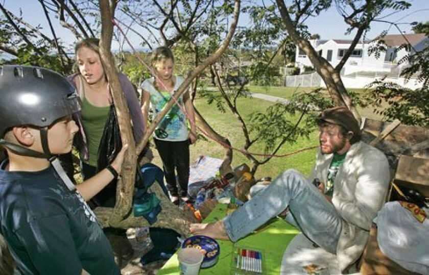 Andrew Watkins sat in a tree in Orpheus Park to prevent it from being cut down. Visiting him Saturday were (from left) Jack McConlogue, 11; Breanna Isley, 13; and Delaney Lindsay, 10. (Charlie Neuman / Union-Tribune)