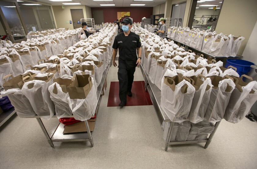 Mama's Kitchen executive chef Jason Martin walks among bags of food that will go out to 607 clients at their commissary on Home Avenue in Fairmont Park on Friday, April 10, 2020. The organization serves the dietary needs of people with HIV, cancer, congestive heart failure and type 2 diabetes.