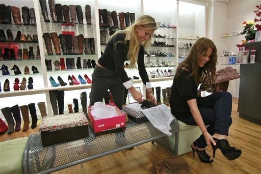 In this photo taken on Monday, Oct. 4, 2010, Dino James, left, and Emily Jones, right, try shoes at the Weiman Shoes store at the Westside Pavilion Shopping Center in Los Angeles. Retailers are reporting surprisingly solid sales gains for September, boosted by back-to-school shopping in the first half of the month.(AP Photo/Damian Dovarganes)