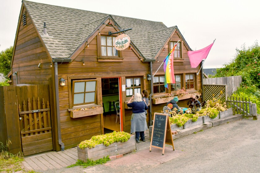 A woman stands outside Fog Eater Cafe, a rustic-looking wooden building.