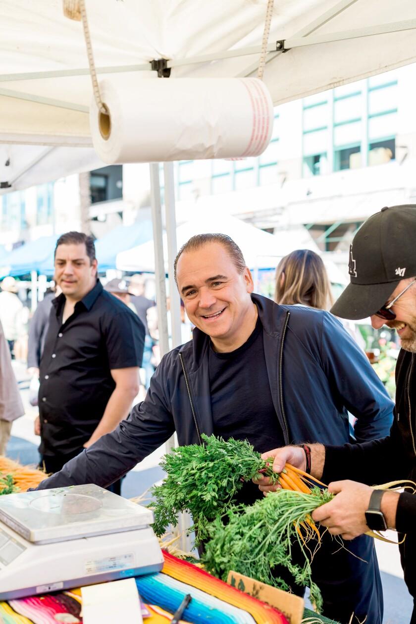 Jean-Georges Vongerichten, center, shops at the Santa Monica farmers market with members of his team, Daniel Del Vecchio, left, and Steve Benjamin.