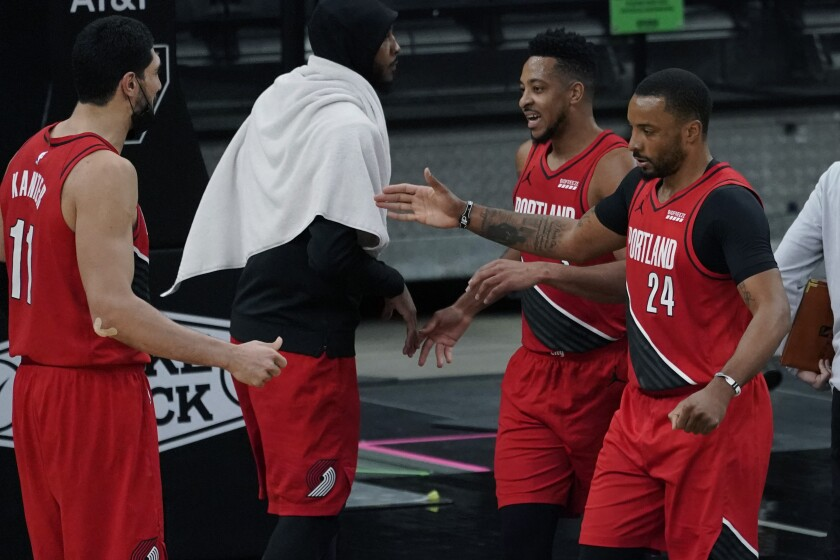 Portland Trail Blazers forward Norman Powell (24) and guard CJ McCollum, second from right, celebrate their win against the San Antonio Spurs with teammates Enes Kanter (11) and Carmelo Anthony, second from left, during the second half of an NBA basketball game in San Antonio, Friday, April 16, 2021. (AP Photo/Eric Gay)