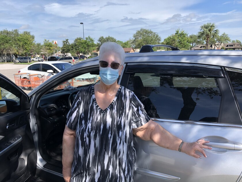 Priscilla Skalka of Pinellas Park, Fla., wearing a surgical mask as she stands by her car.