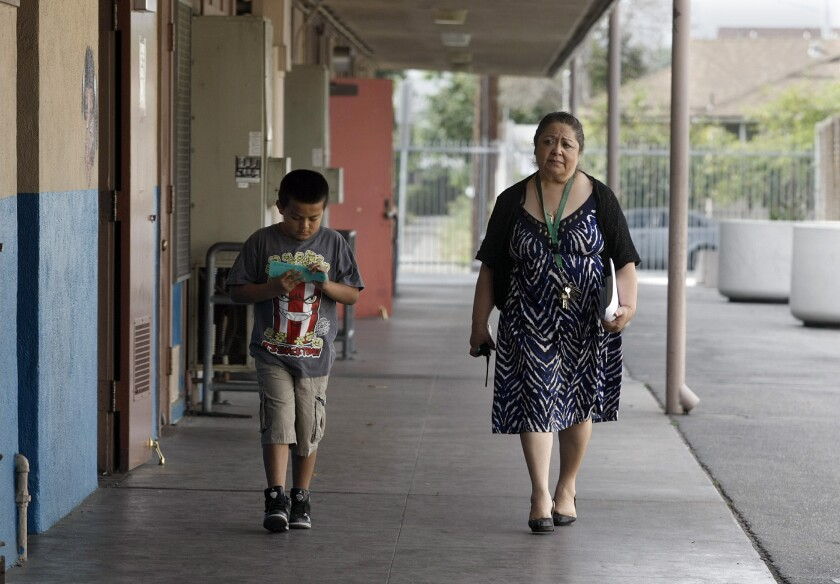 Irma Cobian, right, principal at Weigand Avenue Elementary School, walks with Jose Luis Torres, a 3rd grade student. The Los Angeles Unified School District voted to accept a parent petition to remove Cobian at the low-performing school although she has led efforts to craft a turnaround plan this year that was highly rated by the district.