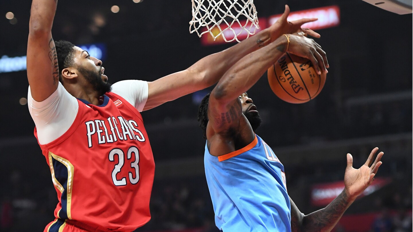 Clippers center DeAndre Jordan grabs a rebound from Pelicans Anthony Davis during the first half of a game Tuesday at Staples Center.