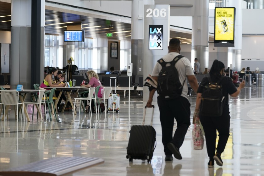 FILE - In this May 24, 2021, file photo, passengers wait for their flights inside the new West Gates at Tom Bradley International Terminal at Los Angeles International Airport in Los Angeles. A groundbreaking ceremony on Monday, June 21, 201, marked the start of construction of an $898.6 million station that will directly connect Los Angeles International Airport to the region's light rail and bus transportation systems. (AP Photo/Ashley Landis, File)