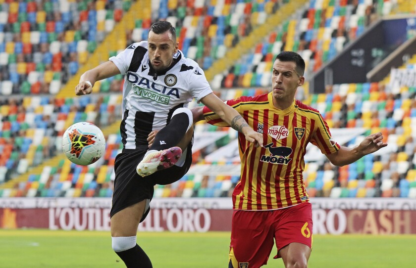 Lecce's Nehuén Paz, right, and and Udinese's Ilija Nestorovski vie for the ball during an Italian Serie A soccer match between Udinese and Lecce at the Dacia Arena stadium in Udine, Italy, Wednesday, July 29, 2020. (Andrea Bressanutti/LaPresse via AP)