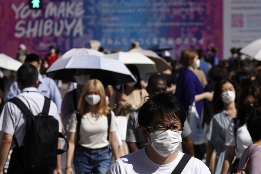Gente con mascarilla para protegerse del coronavirus cruza el paso de peatones de Shibuya, en Tokio