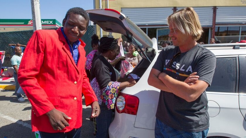 Olivier Virmont, right, who lives in Oceanside looks on as a young man tries on a jacket that is among the clothes that he brought down in his car to give to the Haitians and other migrants at the Padre Chava soup kitchen in Tijuana.