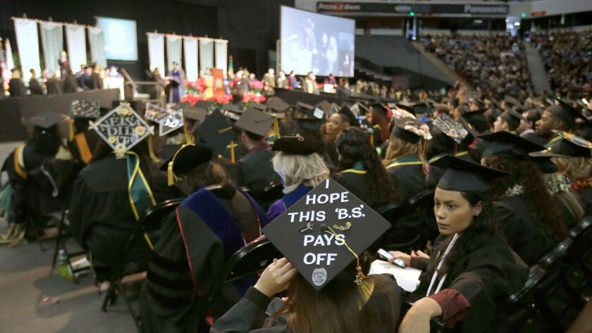 FILE - In this Dec. 17, 2016 file photo a message adorns a students mortarboard during graduation ce