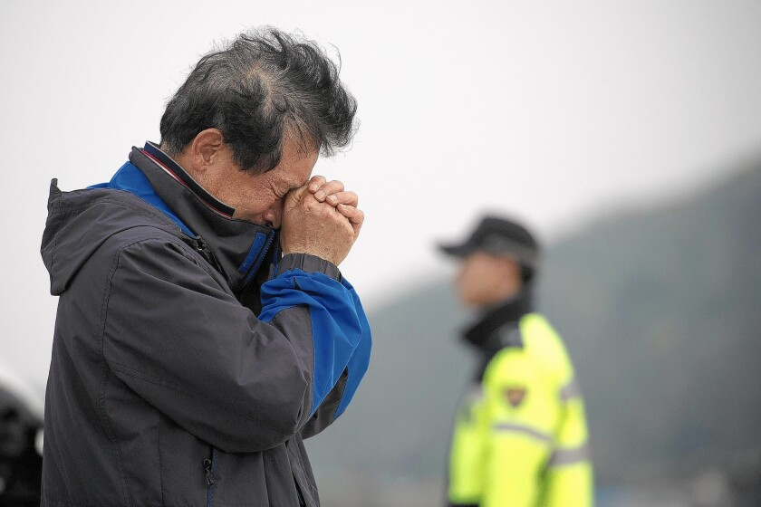 A relative weeps at an area where family members of victims of the South Korean ferry Sewol are gathered, at Jindo harbor on April 21, 2014.