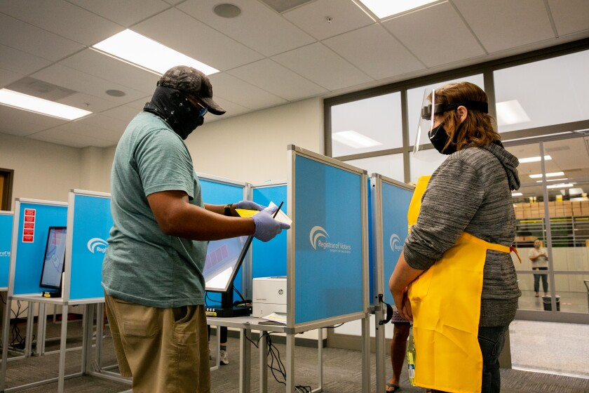 Election worker Rachael Goldstein dons personal protective equipment while helping voter Richard Dew.