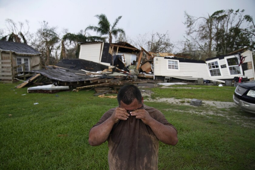 A man stands on a green lawn with rubble in the background.