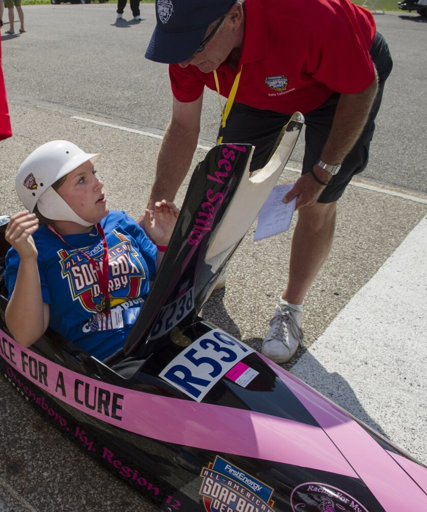 Kelsey Settles of Owensboro, Ky., reacts after being told by Derby volunteers that she is the winner of the Rally Masters Division at the All-American Soap Box Derby in Akron, Ohio, Saturday, July 25, 2015. (AP Photo/Phil Long)