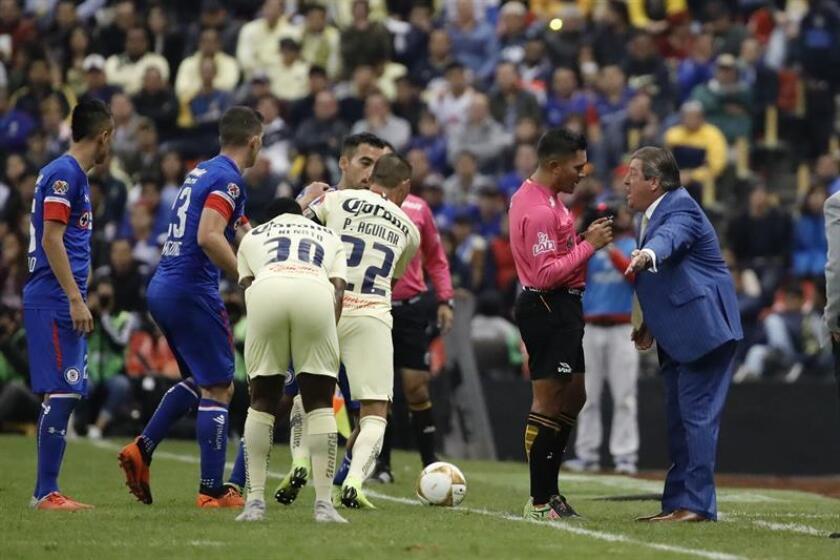 El técnico de América Miguel Herrera (d) discute con el árbitro central Fernando Guerrero (c) durante el juego de ida de la final del torneo mexicano de fútbol celebrado hoy en el estadio Azteca en Ciudad de México (México). EFE