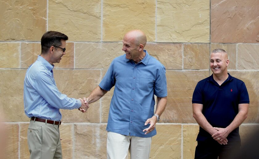 Stephen Whitburn, left, executive director of San Diego Pride shakes hands with Padres CEO Mike Dee as Bob Lehman  of the San Diego Gay Men's Chorus watches them.