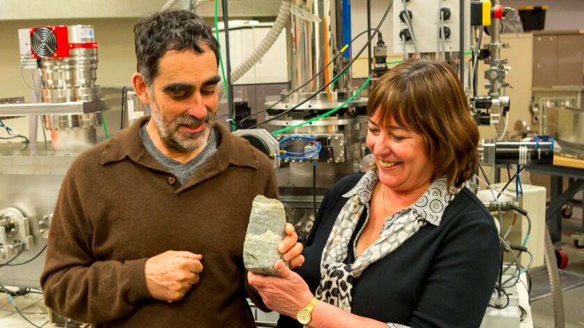 Researchers Allen Nutman, left, and Vickie Bennet display an ancient stromatolite from Isua, Greenland.