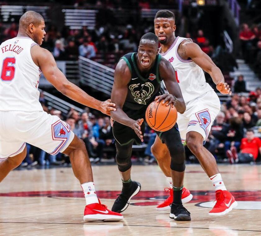 Milwaukee Bucks guard Tony Snell (C) works his way between Chicago Bulls forward Cristiano Felicio of Brazil (L) and David Nwaba (R) in the first half of their NBA game at the United Center in Chicago, Illinois, USA. EFE