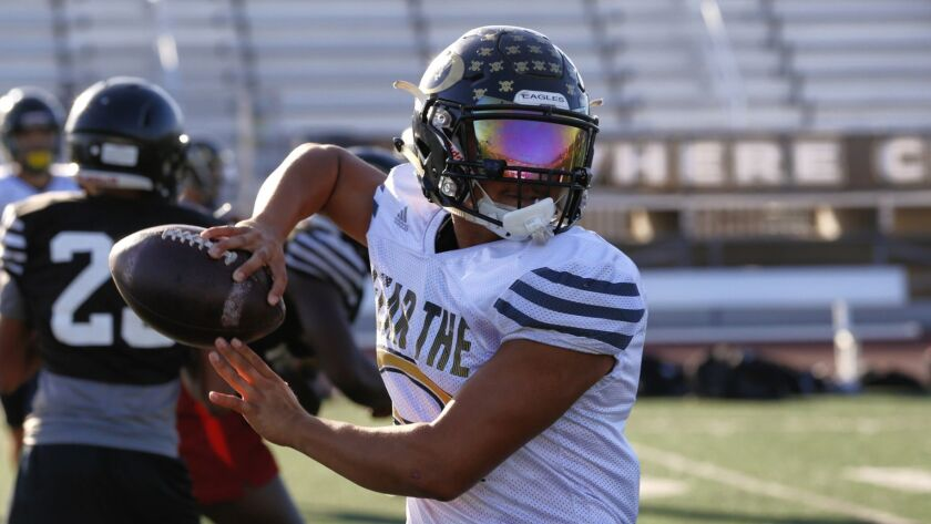Arnold Escano works out at practice Monday at Olympian High. An injury to starting quarterback Lukas Hamilton forced the versatile Escano to take the reins.