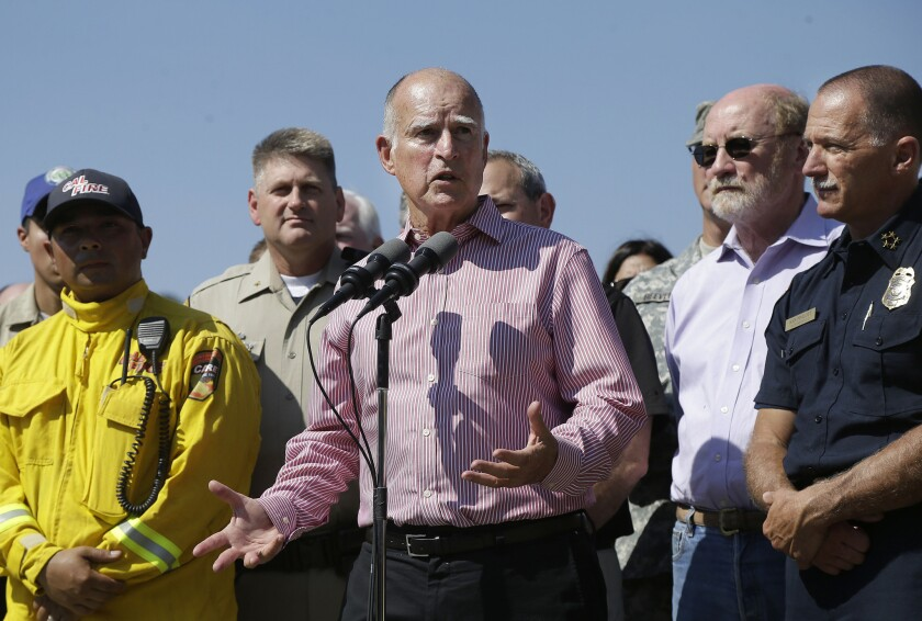 Gov. Jerry Brown, center, surrounded by firefighters and first responders, speaks at a news conference at Cowboy Camp Trailhead during the Rocky fire in August.