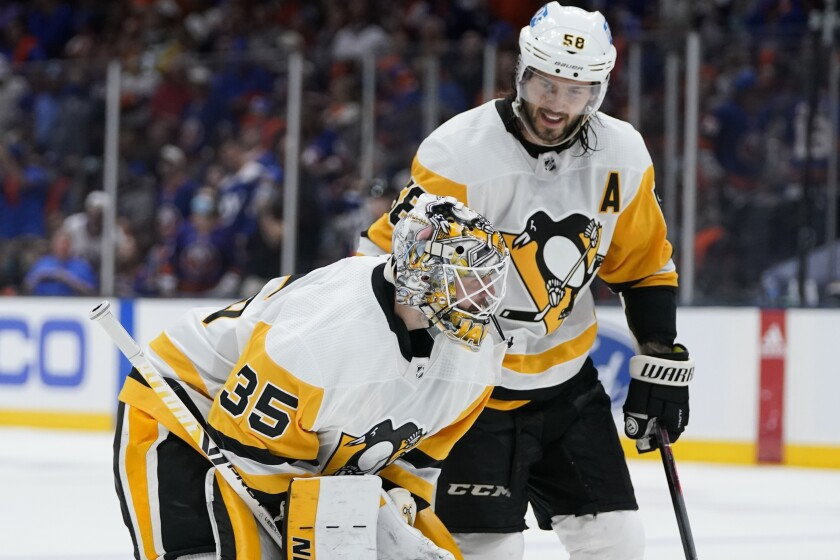 Pittsburgh Penguins' Kris Letang (58) consoles Pittsburgh Penguins goaltender Tristan Jarry (35) during the second period of Game 6 of an NHL hockey Stanley Cup first-round playoff series against the New York Islanders, Wednesday, May 26, 2021, in Uniondale, N.Y. (AP Photo/Frank Franklin II)