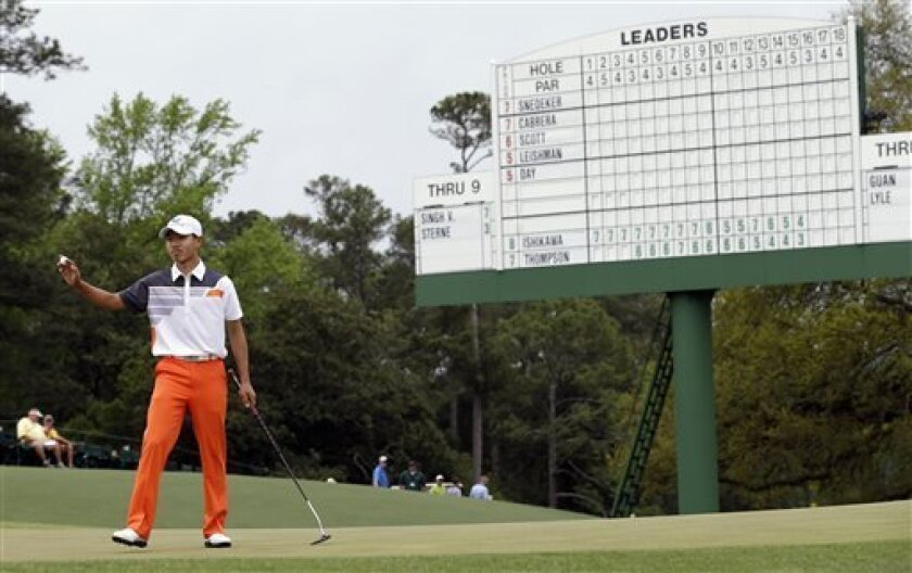 Amateur Guan Tianlang, of China, holds up his ball after putting out on the 18th green during the fourth round of the Masters golf tournament Sunday, April 14, 2013, in Augusta, Ga. (AP Photo/David J. Phillip)