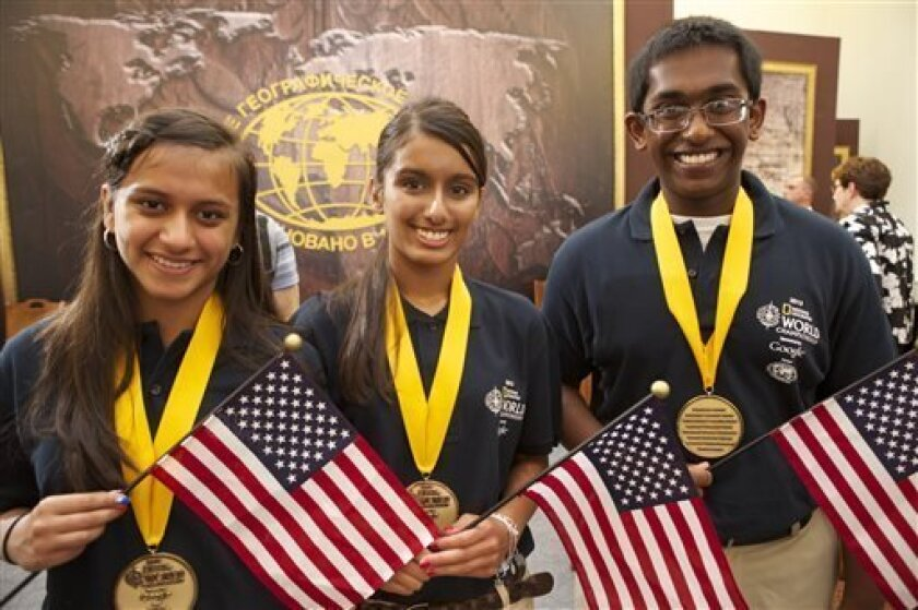This Wednesday, July 31, 2013 photo provided by National Geographic shows Asha Jain, 13, of Minocqua, Wis., Gopi Ramanathan, 15, of Sartell, Minn., and Neelam Sandhu, 14, of Bedford, N.H., members of the U.S. team that edged out Canada and India in the final round of the National Geographic World Championship held in St. Petersburg, Russia. (AP Photo/National Geographic, Rebecca Hale)