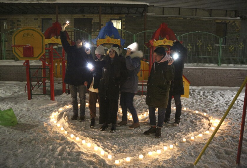 People shine their cellphone flashlights in support of jailed opposition leader Alexei Navalny and his wife Yulia Navalnaya, in the Siberian city of Omsk, Russia, Sunday, Feb. 14, 2021. When the team of jailed Russia opposition leader Alexei Navalny announced a protest in a new format, urging people to come out to their residential courtyards on Sunday and shine their cellphone flashlights, many responded with jokes and skepticism. After two weekends of nationwide demonstrations, the new protest format looked to some like a retreat. But not to Russian authorities, who moved vigorously to extinguish the illuminated protests planned for Sunday. (AP Photo)