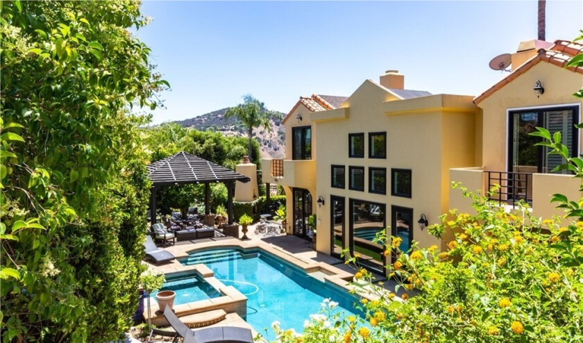 The two-story home features a courtyard with a fountain in front and backyard with a dining gazebo, swimming pool and spa.