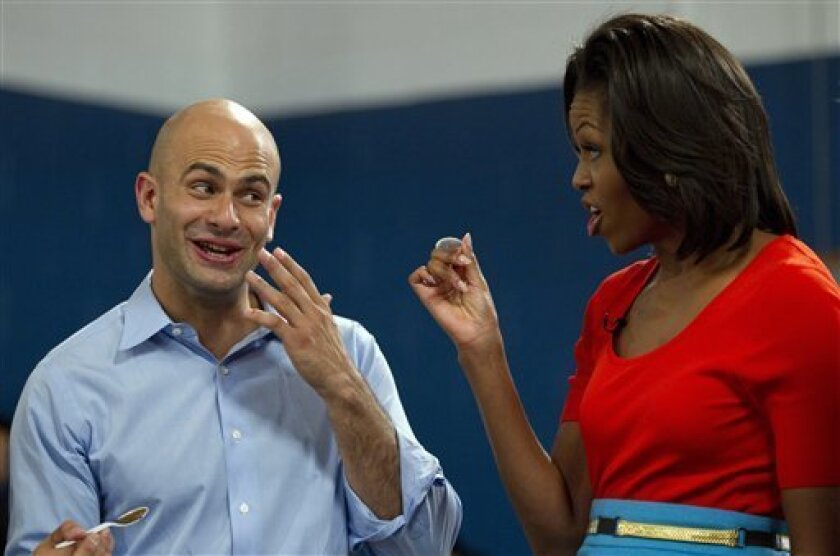 FILE - In this Feb. 10, 2012, file photo first lady Michelle Obama and White House assistant chef Sam Kass taste food in Dallas. Kass, who cooks dinner for President Barack Obama several nights a week, said Tuesday, April 9, 2013, that he will be furloughed as part of across-the-board budget cuts that went into effect in March 2013. (AP Photo/Carolyn Kaster, File)