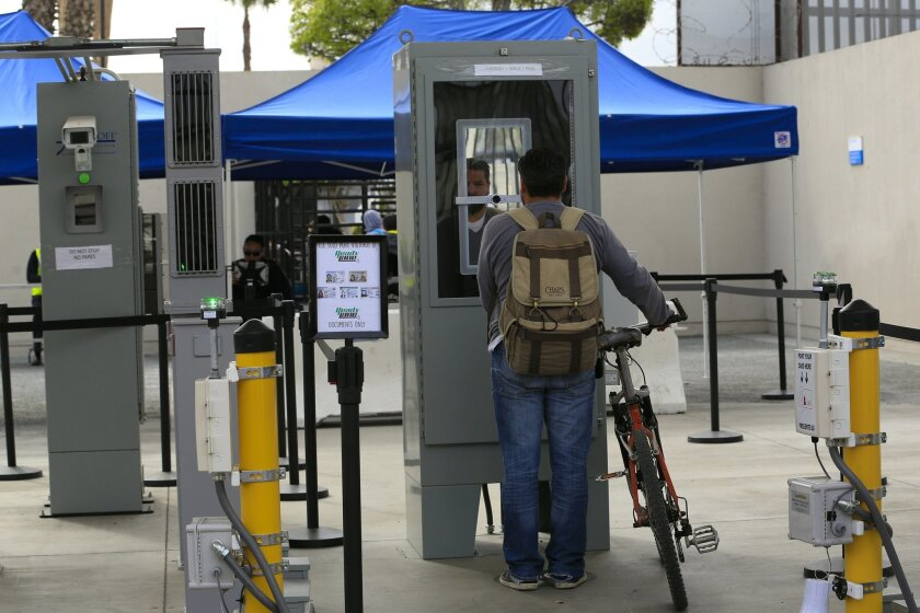 At the Otay Mesa pedestrian crossing a man has his facial and iris biometrics collected from the camera at the Pause and Look device.