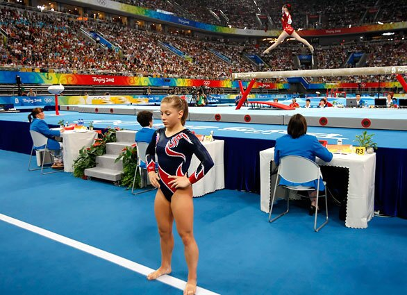 U.S. gymnast Shawn Johnson prepares for her balance beam routine as China's Li Shanshan performs during the finals at Beijing's National Indoor Stadium. Shanshan fell during her routine; Johnson nailed hers for the gold medal.