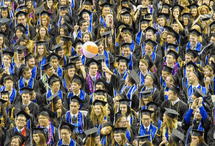 Graduating seniors toss a beach ball during commencement at UCLA. A new report found that students who iidentify as being from Chinese, Japanese, Indian, Vietnamese or Korean families tend to have significantly higher graduation rates at the UC and Cal State systems than do native Hawaiians, other Pacific Islanders and students from Laos.