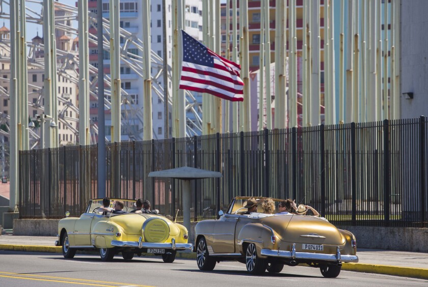 Tourists ride vintage American convertibles past the U.S. Embassy in Havana.
