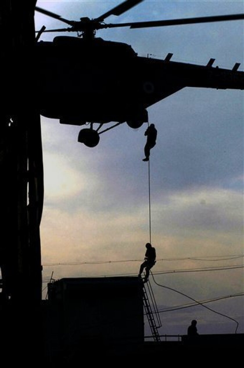 In this Nov. 28, 2008 file photo, National Security Guard commandos come down a rope to reach the top of Nariman House, a location under siege by suspected militants in Mumbai, India. Indian Prime Minister Manmohan Singh said Tuesday, Jan. 6, 2009, that he did not believe the November Mumbai attac