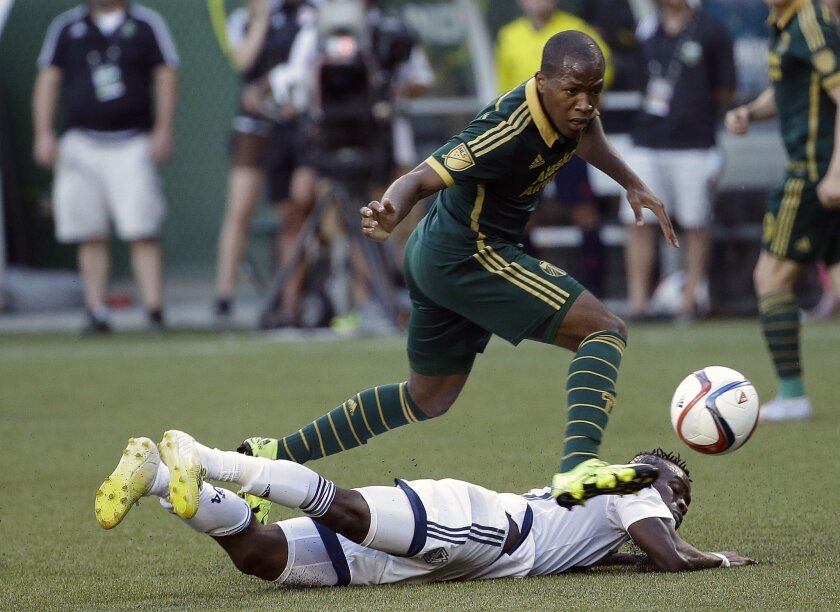 FILE - In this July 18, 2015, file photo, Portland Timbers forward Darlington Nagbe, top, leaps over Vancouver Whitecaps midfielder Gershon Koffie as he chases the ball during the first half of an MLS soccer game in Portland, Ore. Nagbe is back with Portland for their match against Dallas after his first call up to the U.S. national team. (AP Photo/Don Ryan, File)