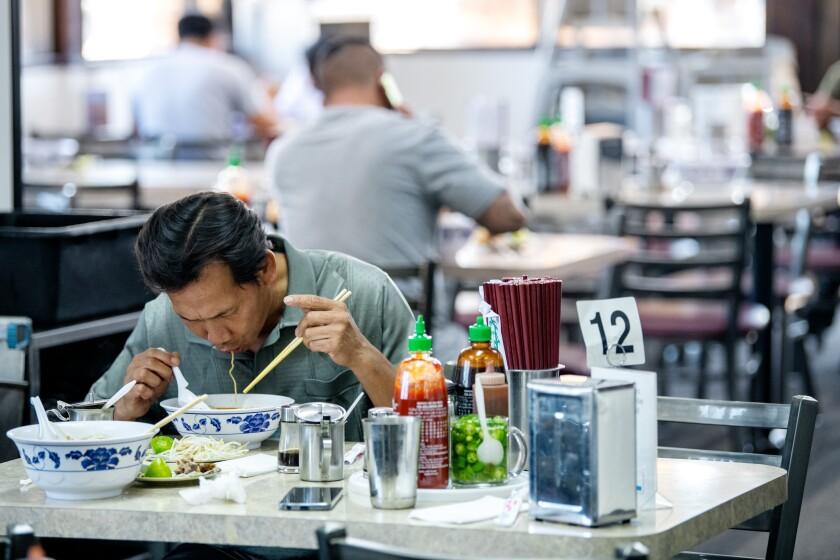 Customers dig into bowls of hu tieu at Trieu Chau Restaurant in Santa Ana.