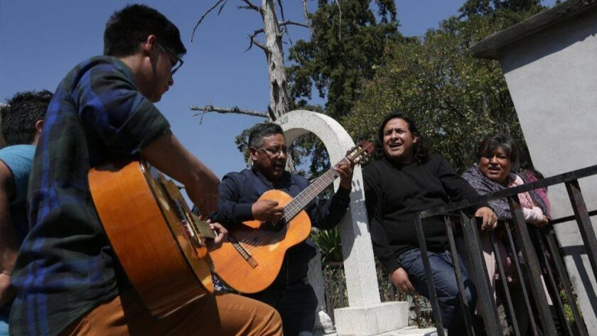 On the one-year anniversary of his death, members of Eduardo Hernandez's family gather at his grave in Nicolas Romero, Mexico, to play guitar and sing.